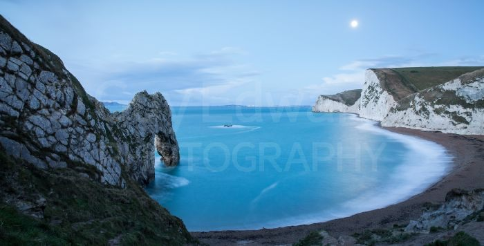 The full moon setting over Bat's Head viewed from Durdle Door.